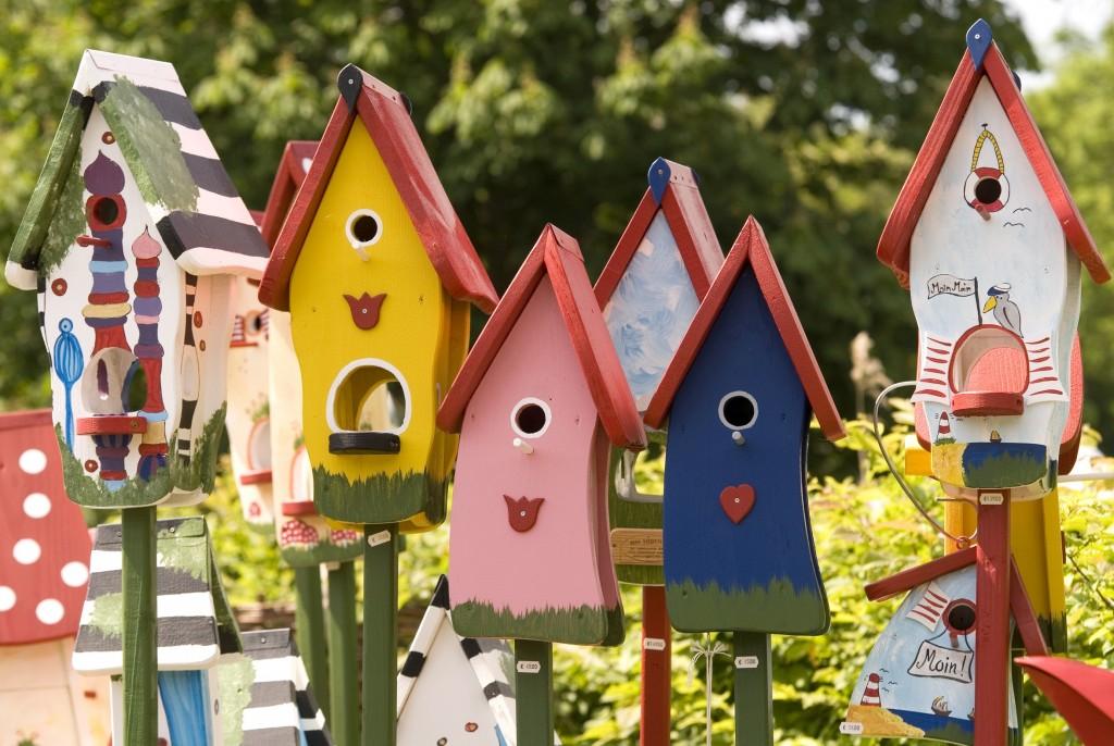 Eine Reihe von bunt bemalten und individuell gestalteten Vogelhäusern im Sonnenlicht